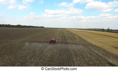 Tractor plowing the fields corn in spring. aerial shot -...