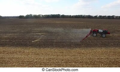 red tractor plowing the fields corn in spring. aerial shot -...
