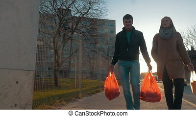 Man and woman returning home after shopping - Slow motion...