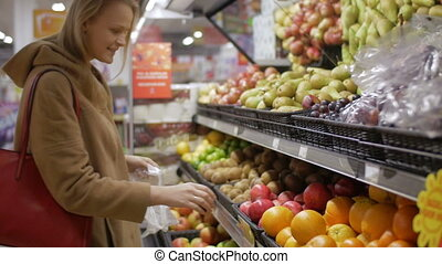Young woman choosing fresh fruit in the supermarket