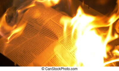 Newspaper in the flames of fire - Slow motion close-up shot...