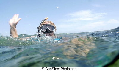 Woman in snorkel sending greeting from the sea - Slow motion...