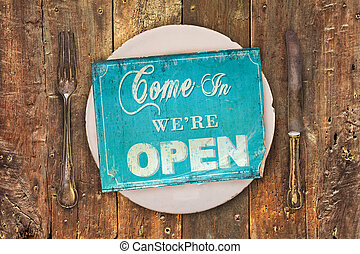 Vintage open sign on a dinner plate with fork and knive on...