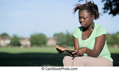African woman sitting on a log reading a book closer frame