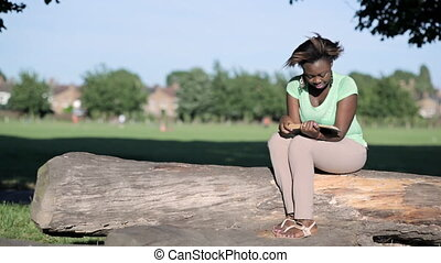 African woman reads on a log - African woman sitting on a...