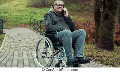 Disabled man talking on smartphone in wheelchair