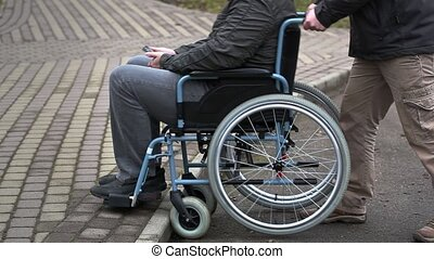 Assistant try pushing the wheelchair with disabled man on...