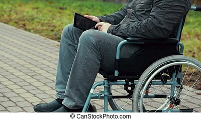 Disabled man with tablet PC in wheelchair