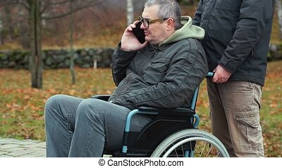 Disabled man talking on smartphone in wheelchair with...
