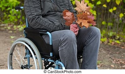 Disabled man with autumn leaves in wheelchair at outdoor