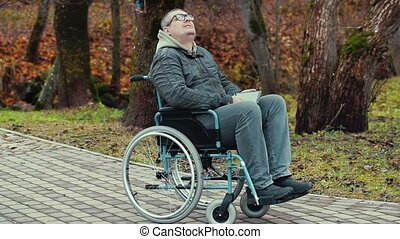 Disabled man in wheelchair breathe fresh air at outdoors