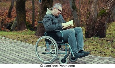 Disabled man with book in wheelchair at outdoor