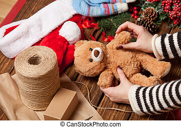 Woman holding teddy bear toy before wrapping. High point of...