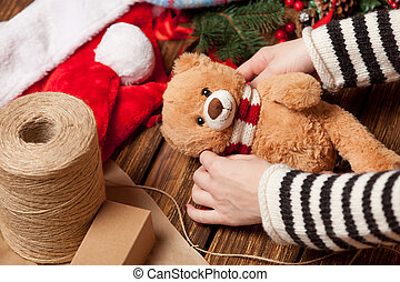 Woman holding teddy bear toy before wrapping High point of...