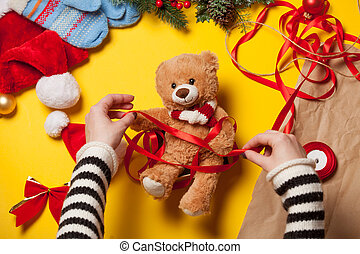woman hands and teddy bear toy - Woman have wrapping a teddy...