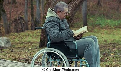 Disabled man reading book in wheelc