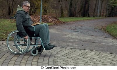 Disabled man using wheelchair on path at outdoor in the park