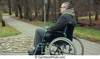 Disabled man in wheelchair waiting for assistance on path in...