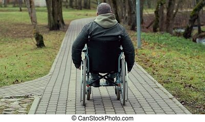 Disabled man in wheelchair on path in the park
