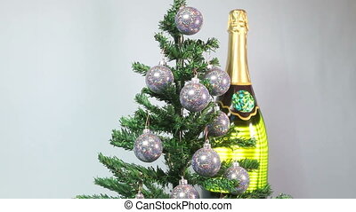 New Years balls on New Year tree and huge bottle of...