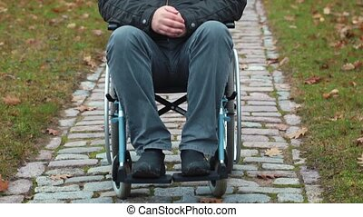 Disabled veteran in wheelchair at cemetery in autumn