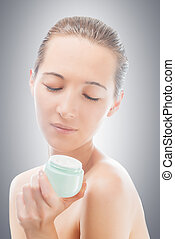 Caring for facial skin - Woman looks at a jar of cream,...
