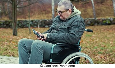 Disabled man in wheelchair on path using tablet PC