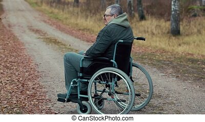 Disabled man in wheelchair on the road waiting for...