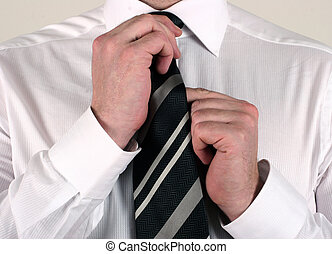 Business man adjusting tie - well dressed business man...