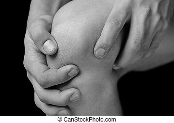 Pain in male knee - Man is touching his knee joint due to...