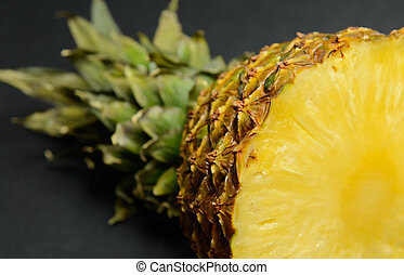 Half pineapple - Half of juicy pineapple on a black table,...
