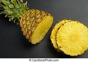 Pineapple round slices on a black table