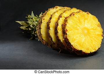 Fresh pineapple - Round ripe pieces of pineapple on a black...