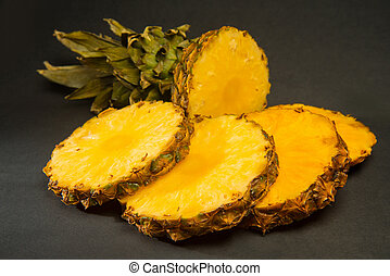 Pieces of pineapple - Sliced ripe pineapple on a black...