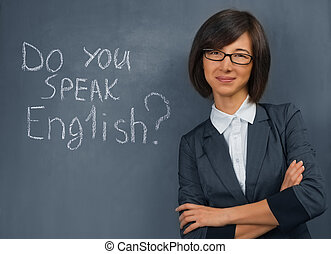 Teacher of English - Young woman in a suit standing near the...