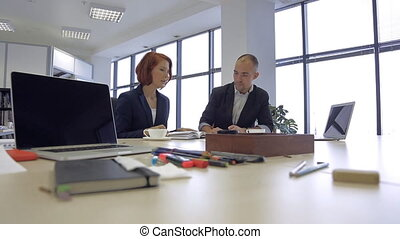 Assistant Producer, Writer, talking with businessman, which is interesting to readers, in his office.