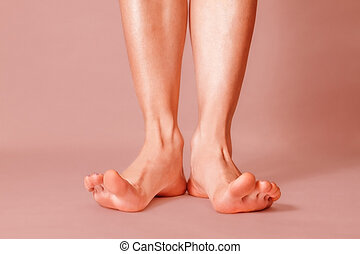 Healthy female feet with splayed fingers on pink background