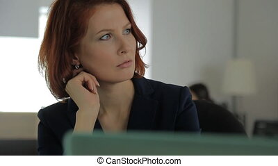 Businesswoman with red hair and red lips in a jacket sits in a large bright spacious office and talking with his client.