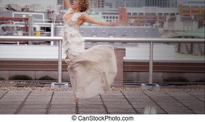 Bride dances on a terrace - Bride enjoys the sunshine on an...