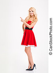 Beautiful happy woman in red santa claus costume pointing...