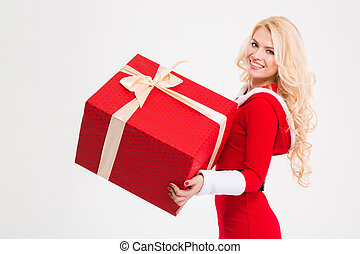 Cheerful female in santa claus clothes holding big red...