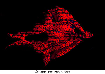 The body of woman with red pattern and its reflection - The...