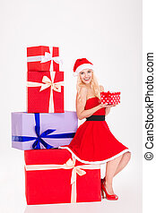 Positive girl in red santa claus dress and hat sitting -...