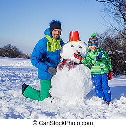 Boy and his father with a snowman