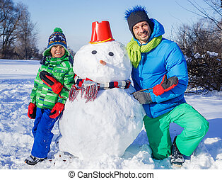 Boy and his father with a snowman - Little boy with his...