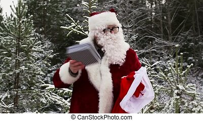 Santa Clause with gift box in the snowy woods