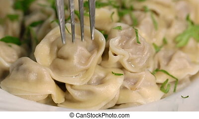 Dumplings, a national Russian dish - A man is taking a...