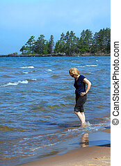 Enjoying Lake Superior - Woman rolls up her jeans and wades...