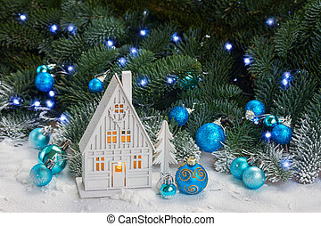 White christmas house with blue decorations and evergreen...