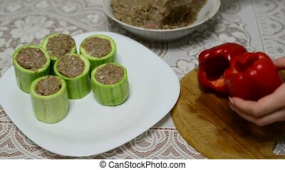 Woman prepares zucchini and pepper stuffed  with meat